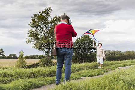 senior man filming wife flying kite