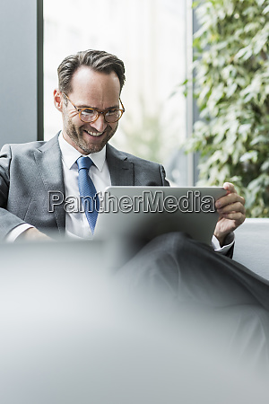 businessman sitting in lobby using laptop