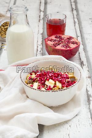 fruehstueck mit fruchtmuesli mit granatapfelsamen milchflasche