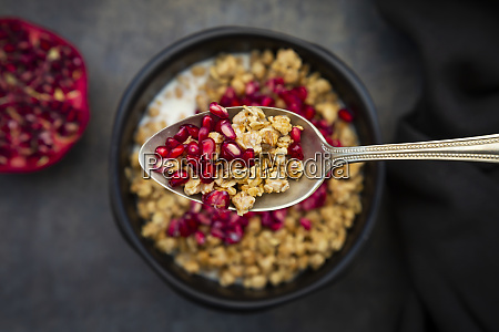 spoon of granola with pomegranate seed