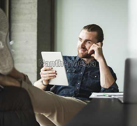 businessman sitting in office with feet