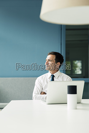 confident businessman with laptop on table