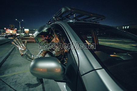 spaceman waving out of car at