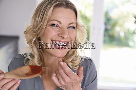 portrait of happy woman tasting tomato