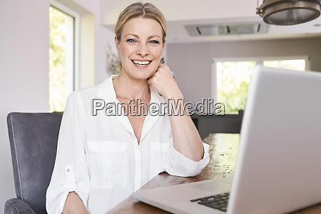 portrait of smiling businesswoman using laptop