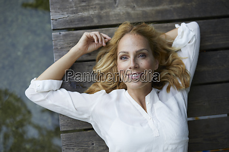portrait of smiling blond woman lying