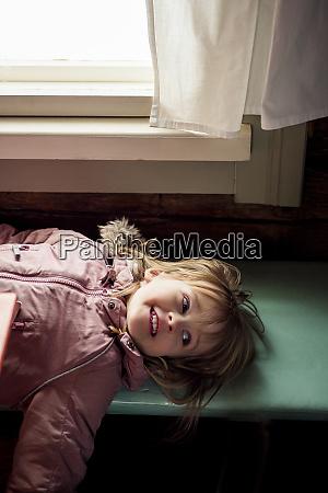 portrait of smiling little girl lying