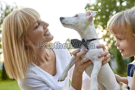 happy, woman, with, daughter, holding, dog - 26522013