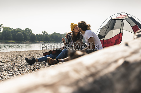 young couple with guitar kissing at