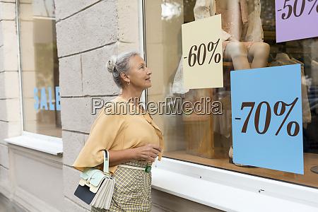 smiling senior woman looking in shop