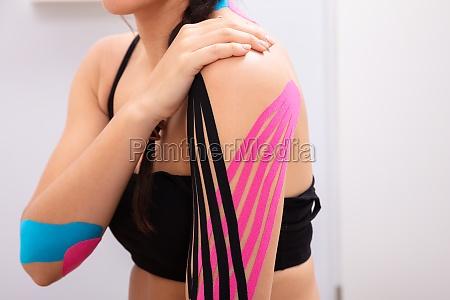 frau hat physio therapie tape auf