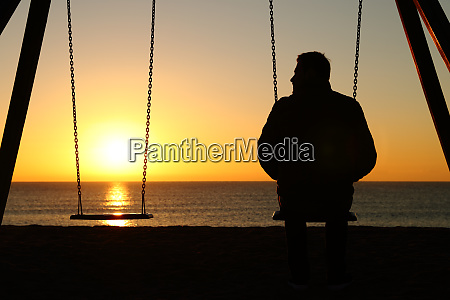 man alone on a swing looking