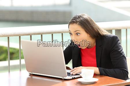 amazed executive reading good news outside