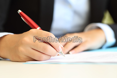 businesswoman hands writing in a document