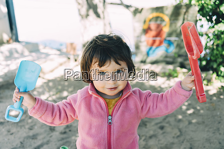baby girl playing with sand and