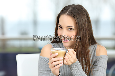confident woman posing holding a coffee