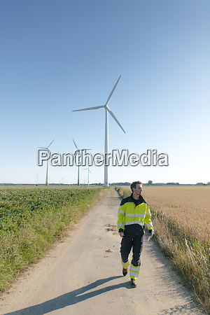engineer walking on field path at
