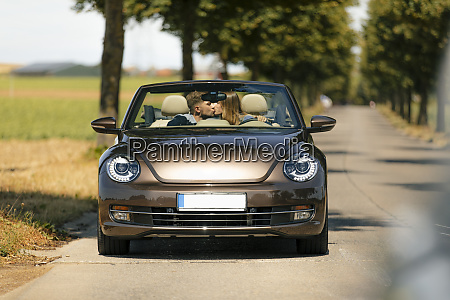 couple kissing in convertible car on