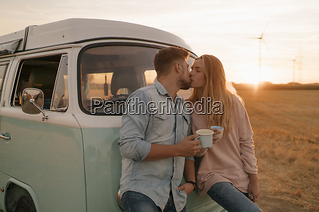 young couple kissing at camper van