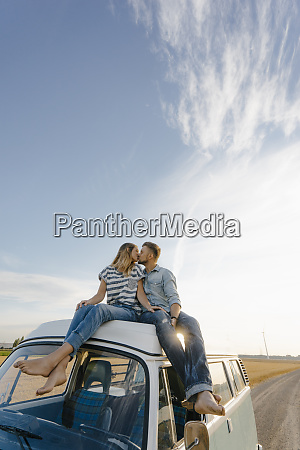 couple kissing on roof of a