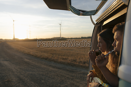 couple brushing teeth in camper van
