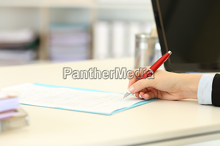 executive hand signing a form or