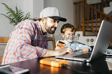 vater und sohn mit laptop zusammen