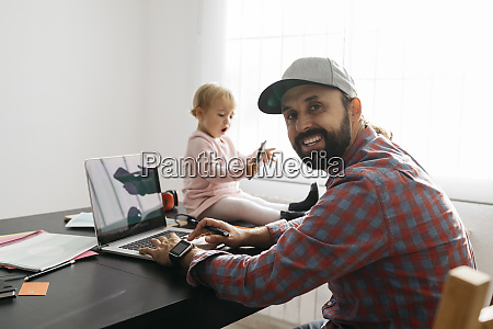 father working from home using laptop