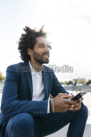smiling young businessman sittimg outdoors holding