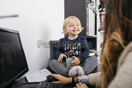 mother working at home with little