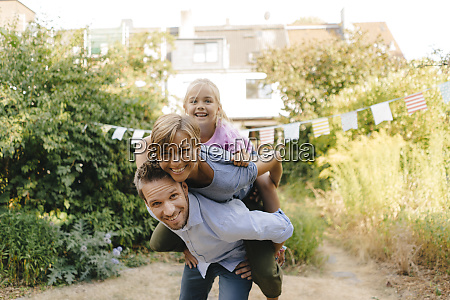 happy father carrying family piggyback in