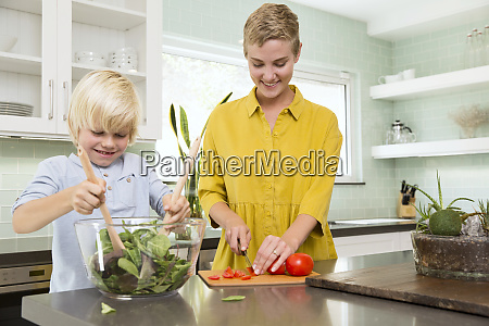 smiling mother and son preparing salad