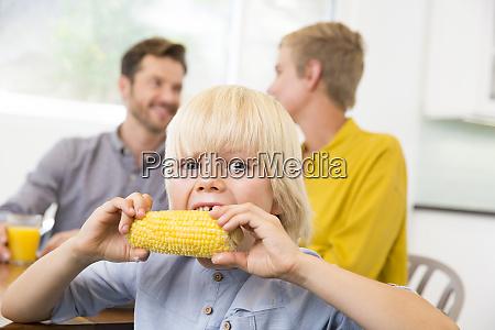 boy eating corn cob in kitchen