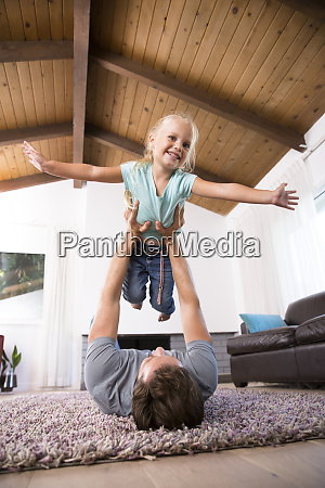 father playing with daughter on carpet