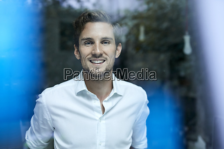 portrait of smiling young businessman behind