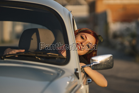 young woman driving vintage car in