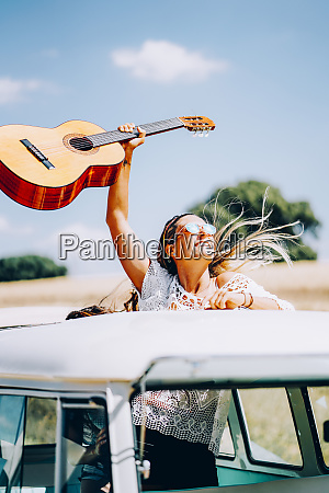 happy young woman holding her guitar