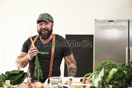 vegan man holding carrot in his