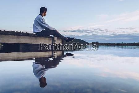 young man sitting at lake inari