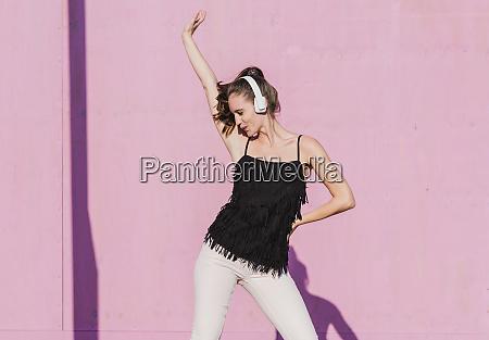 happy young woman wearing headphones dancing