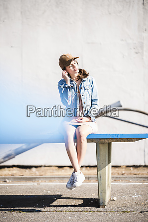 relaxed young woman sitting on table
