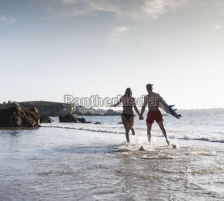 france brittany young couple with surfboard