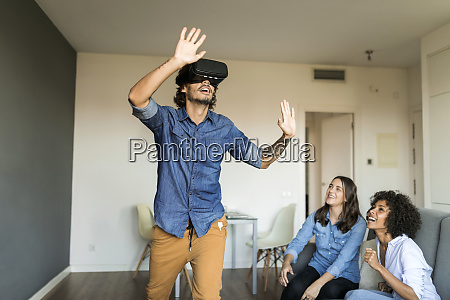 two women watching man with vr