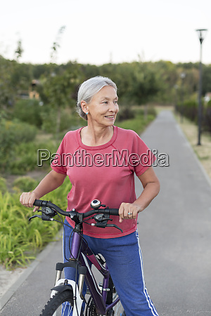 senior woman with bicycle on bicycle