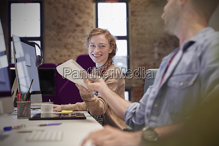 young man helping colleague sitting at