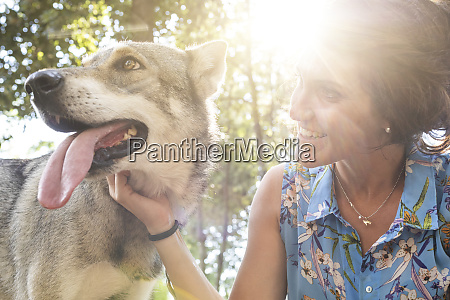 smiling young woman stroking her dog