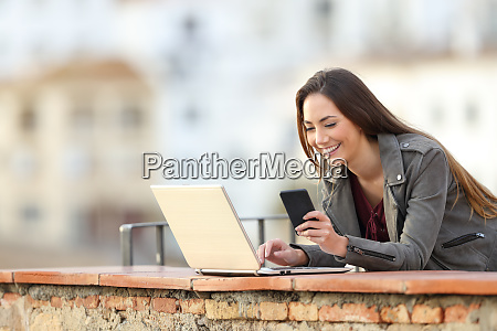 happy woman using phone and laptop