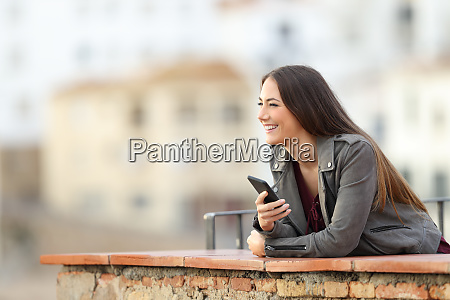 happy woman holding smart phone contemplating
