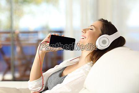 girl listening music and showing phone