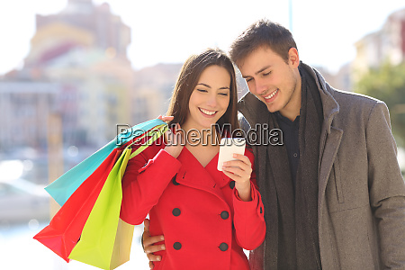 tourists consulting phone holding shopping bags
